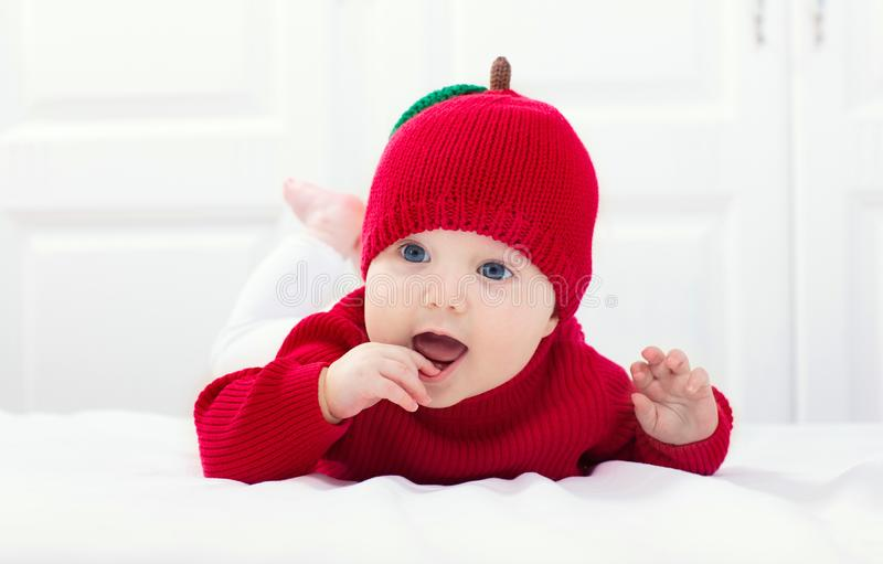 Baby in apple hat. Kid on bed. Child at home royalty free stock photos