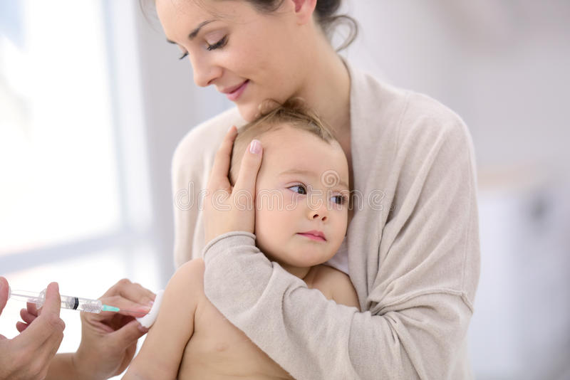 Baby in the arms of her mother getting vaccinated stock images
