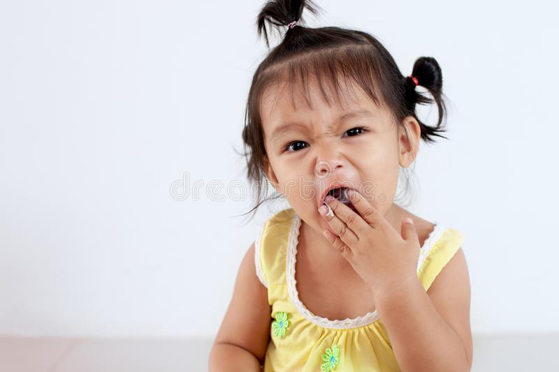 Baby asian child girl eating noodle by herself and making a mess on her face and hand royalty free stock photo