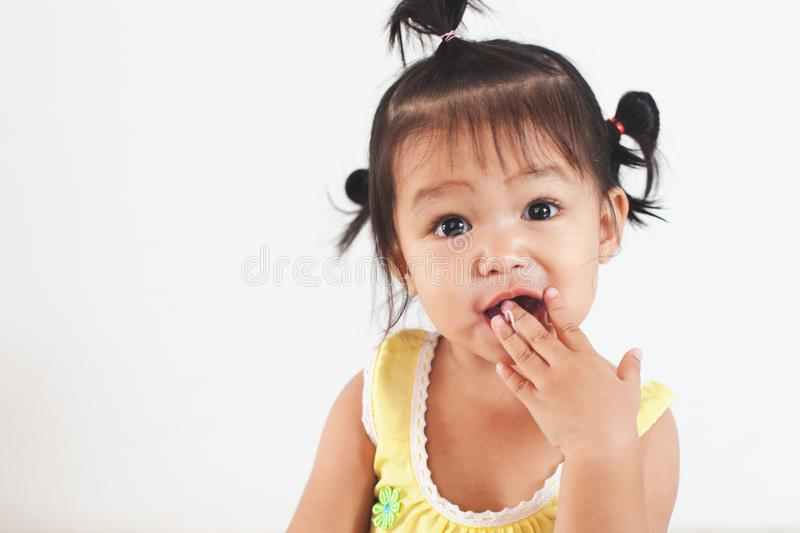 Baby asian child girl eating noodle by herself and making a mess on her face and hand royalty free stock photography