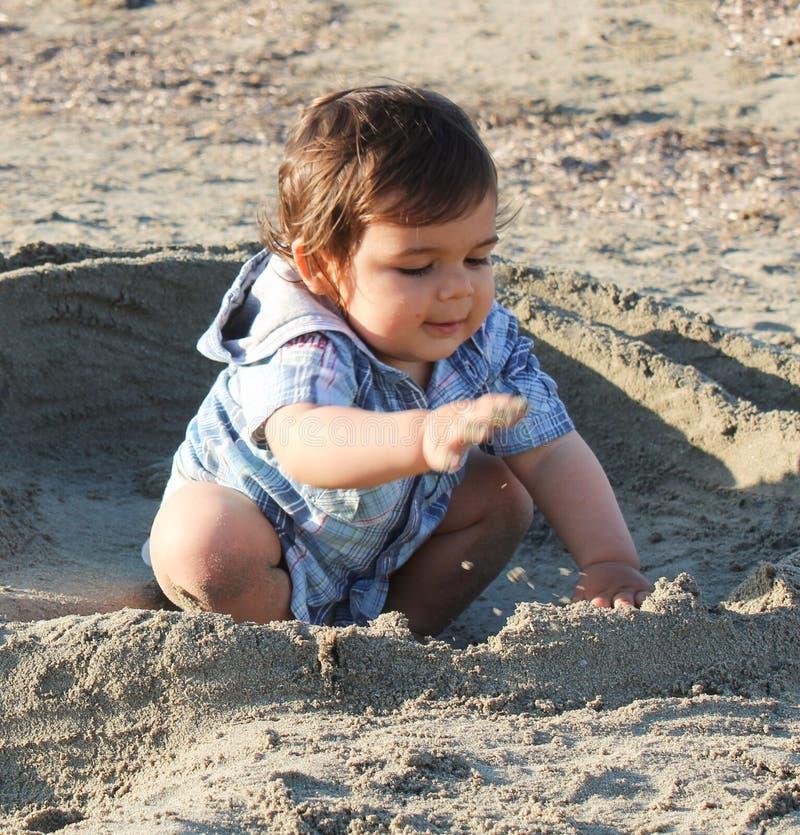 Baby auf dem Strand, der mit Sand spielt lizenzfreie stockbilder