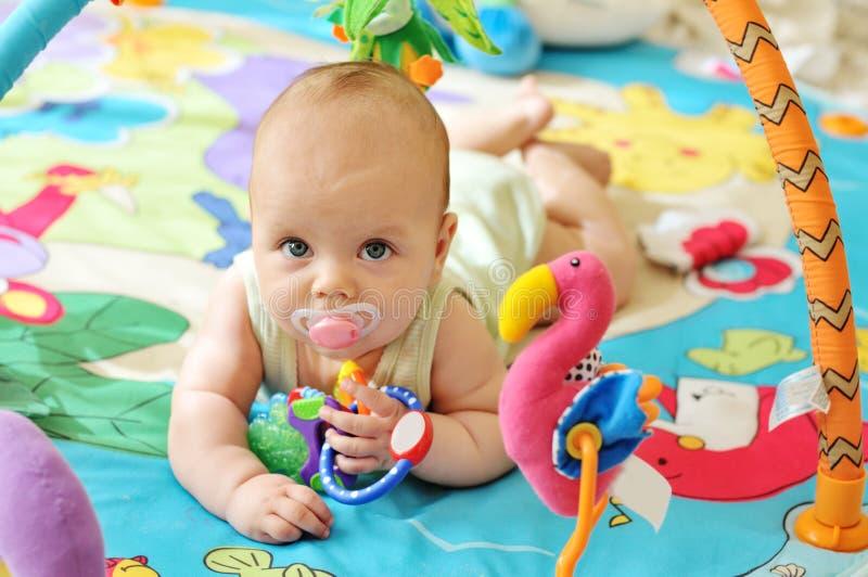 Baby auf der Spielzeugwolldecke lizenzfreie stockbilder