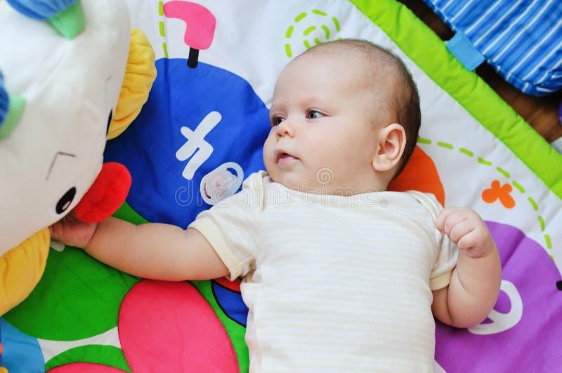 Baby auf der Spielzeugwolldecke stockfotografie