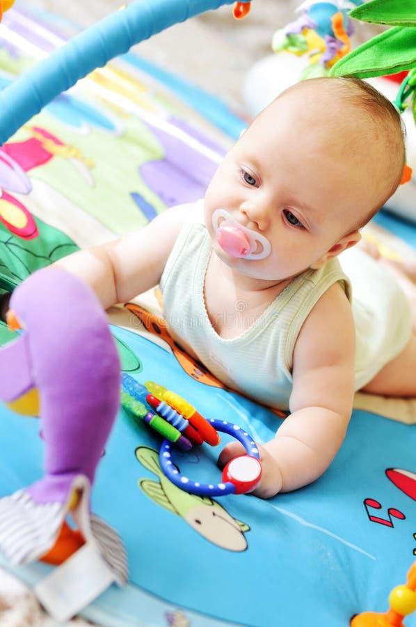 Baby auf der Spielzeugwolldecke stockbild
