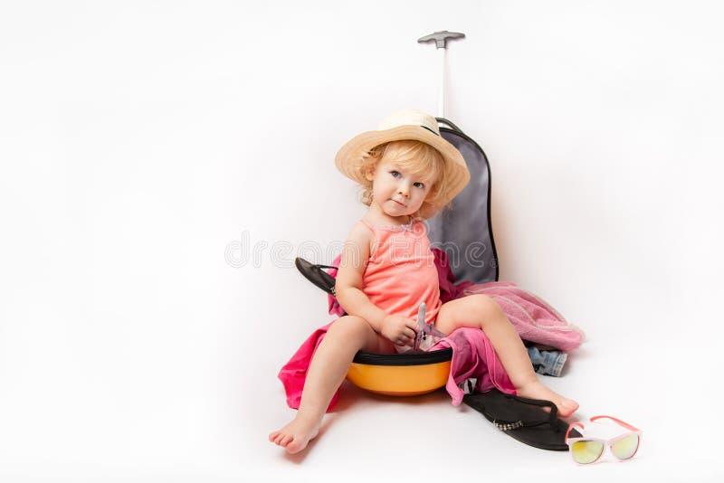 Baby auf Reise-Koffer, Kind sitzen in reisendem Gepäck, Kind in Ferien-Gepäck Reise- und Abenteuerkonzept stockfotografie