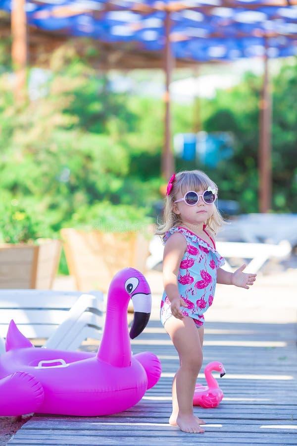 Baby auf Strand mit dem rosa Flamingo gekleidet in der stilvollen schwimmenden Abnutzung, die auf Bretterboden aufwirft Szene im  stockbilder