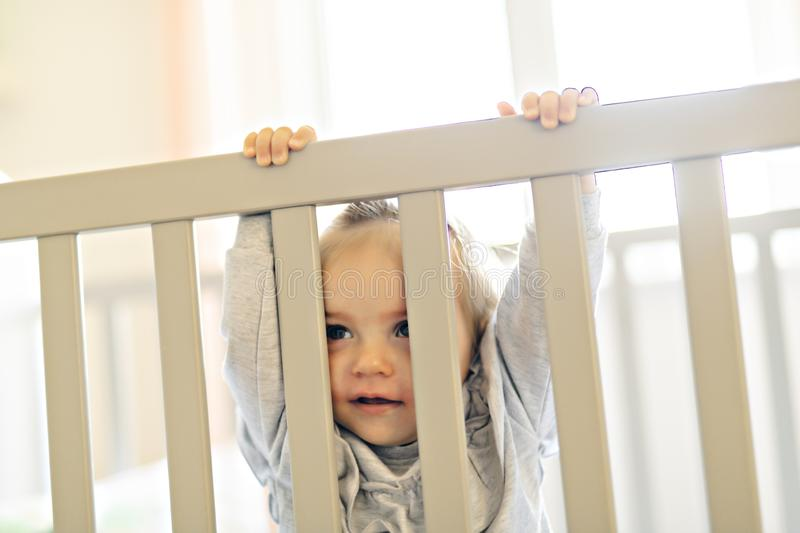 Cute baby baby on the baby room crib. A Baby on the baby room crib royalty free stock photo