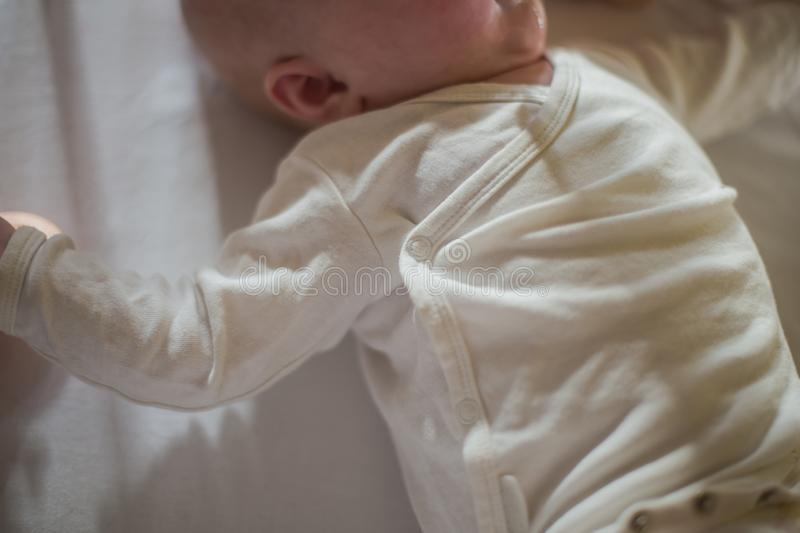 The baby is on the back and touches the toy. White body suit on newborn. Comfortable clothes for newborn. child stuck out his royalty free stock image
