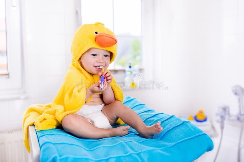 Baby in badhanddoek met tandenborstel stock foto's