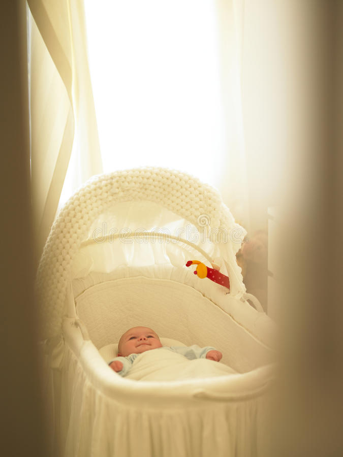 Baby in Bassinet. With curtains fluttering around it. Vertically framed shot stock photos