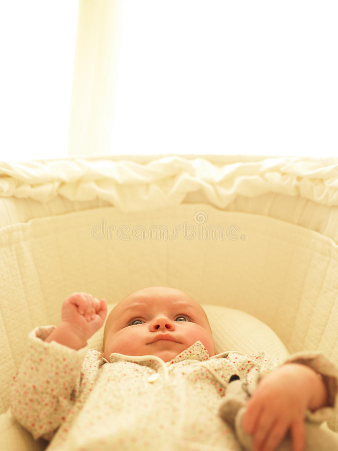 Baby in Bassinet. With toys. Vertically framed shot stock photo