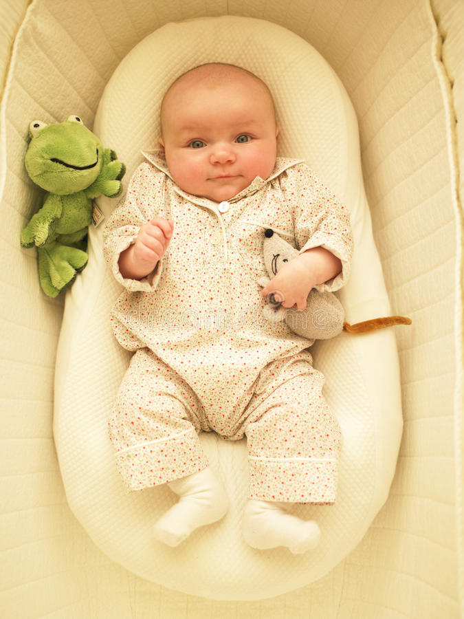 Baby in Bassinet. With toys. Vertically framed shot stock photography