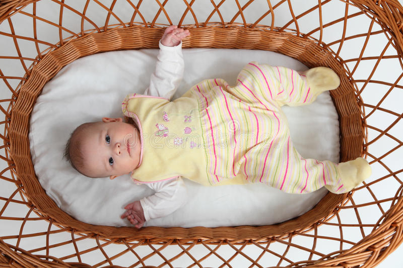 Baby in bassinet. Little baby girl lying in a bassinet royalty free stock image