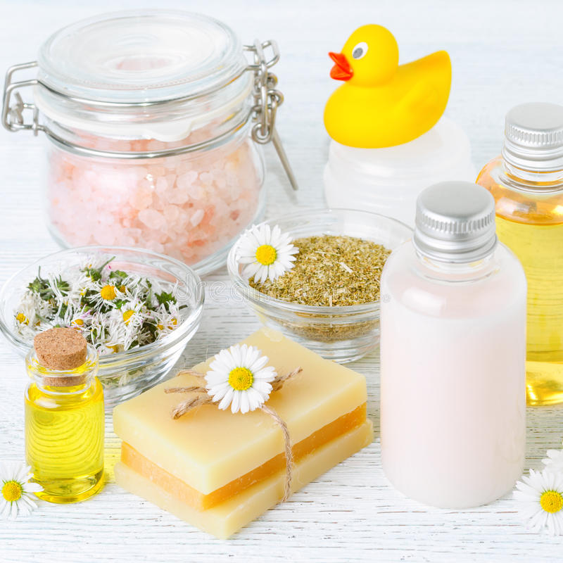 Baby bath with chamomile oil, flowers, soap, salt and organic cosmetics, square. Baby bath with chamomile oil, flowers, soap, salt and organic cosmetics royalty free stock photo