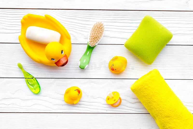 Baby bath set with yellow rubber duck. Soap, sponge, brushes, towel on white wooden background top view. Baby bath set with yellow rubber duck on white stock image