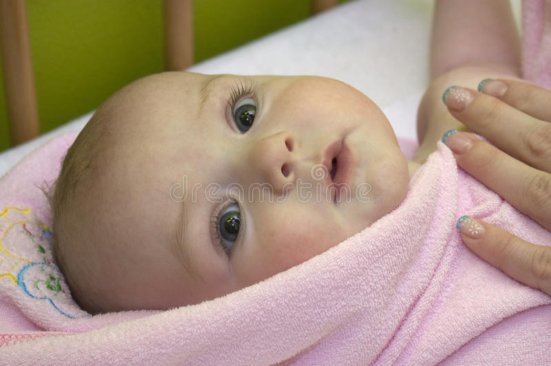 Baby after bath in towel stock image