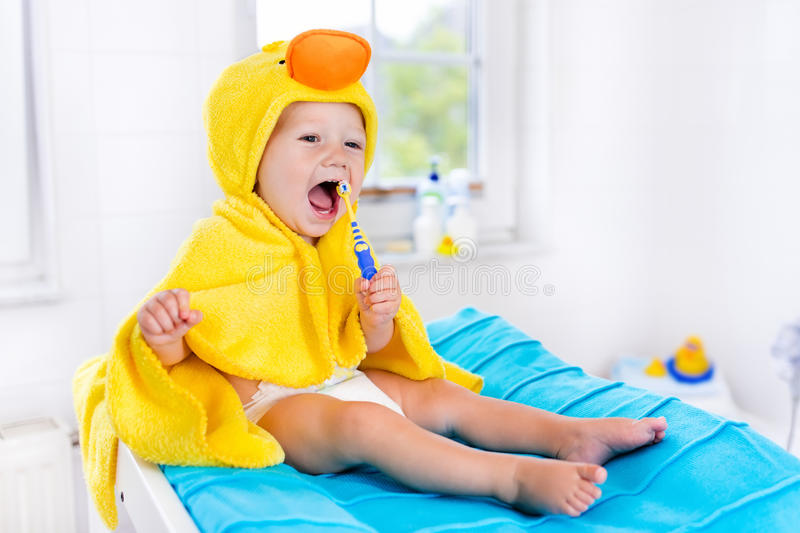 Baby in bath towel with tooth brush stock photo