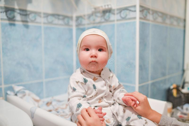 Baby after bathing. Little 8 months old baby after bathing on changing mat.  stock images