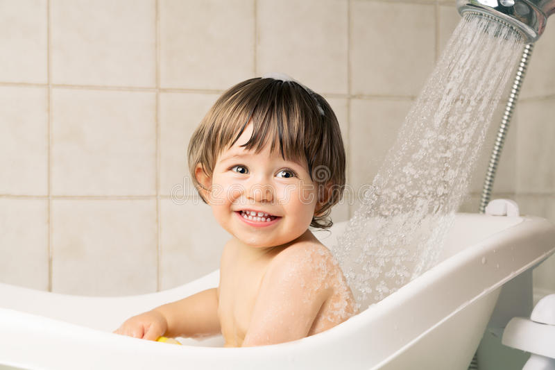 Baby bathing. Smiling beautiful baby boy bathing in a bathtub with shower at home stock photography