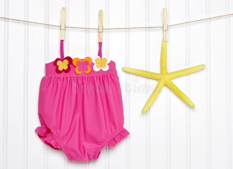 Baby Bathing Suit and Starfish on a Clothesline royalty free stock images