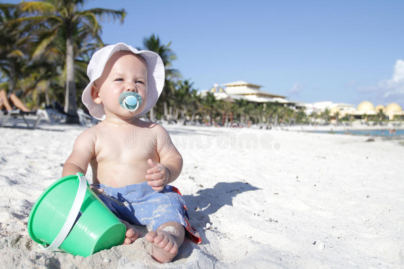 Baby on Beach. Baby boy playing in sand on a tropical beach royalty free stock photography