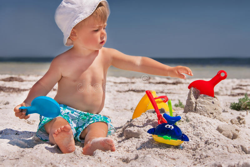 Baby at the beach. Caucasian baby (boy) is sitting at the beach. Close up, outdoor royalty free stock photos