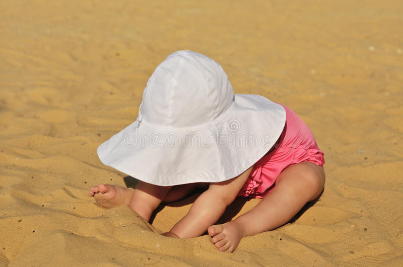 Baby on the beach. Fashion baby on the beach playing with sand royalty free stock image
