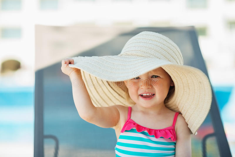 Baby in beach hat sitting on sun bed. Attractive baby girl in beach hat sitting on sun bed royalty free stock images