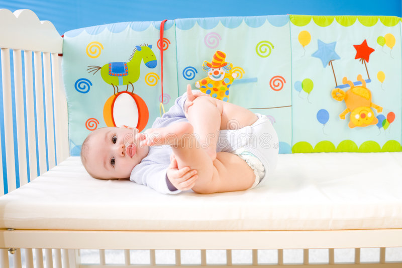 Baby in bed. Cute baby boy (4 months old) lying on back in baby bed stock image