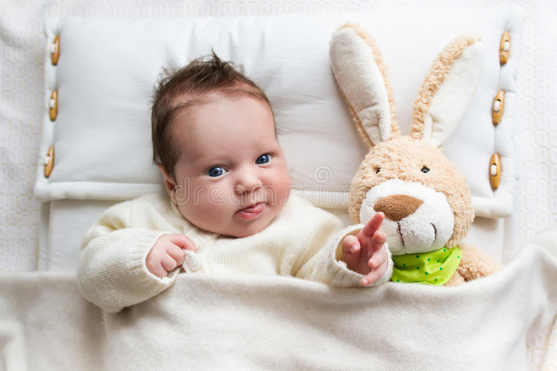 Baby in bed with bunny toy stock images
