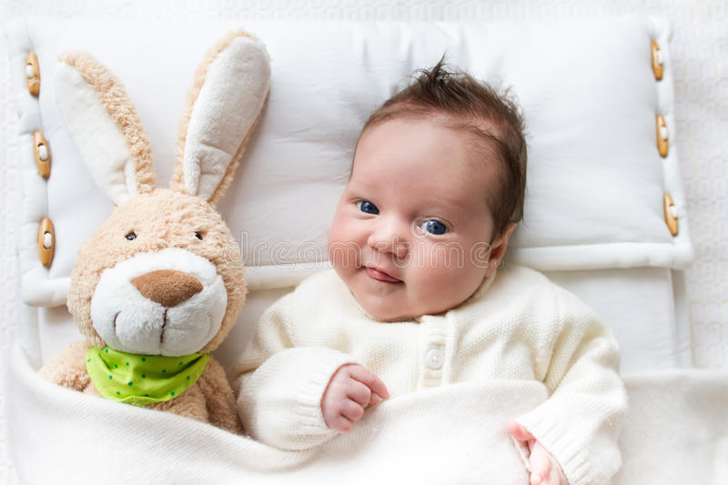 Baby in bed with bunny toy stock image