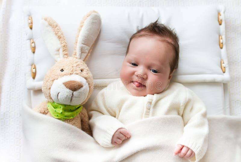 Baby in bed met konijntjesstuk speelgoed stock foto's