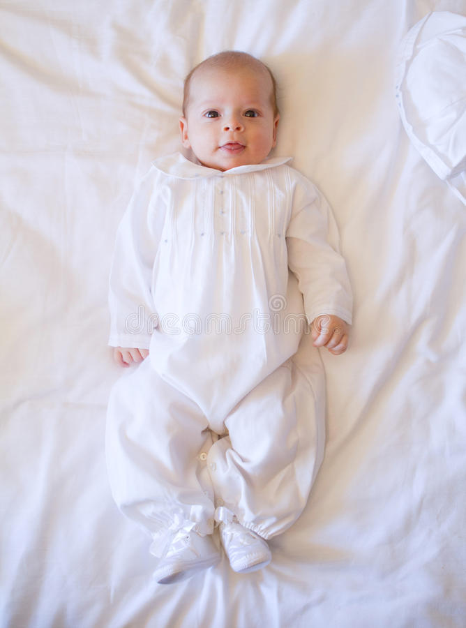 Baby on bed. Newborn baby dressed in white lying on white sheets bed stock photo