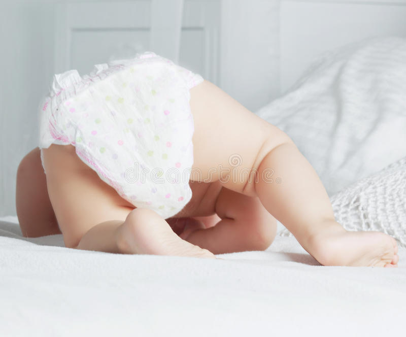 Baby in bed. One year old baby wearing diapers in bed at home stock photography