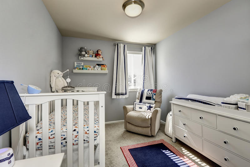 Baby bedroom interior. Gray walls and white wooden furniture. Baby bedroom interior, boy's room. Gray walls and white wooden furniture: chest of drawers, crib stock photos