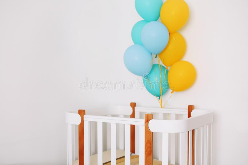 Baby bedroom interior. Minimalistic baby room interior. Festive balloons in front of baby bed. Baby birthday celebration concept. stock photos