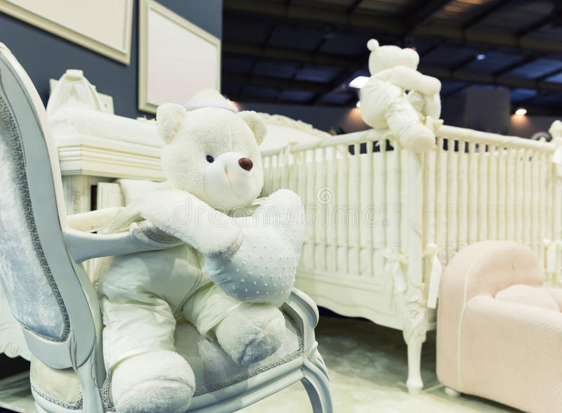 Baby bedroom with white teddy bear. On the chair stock photo