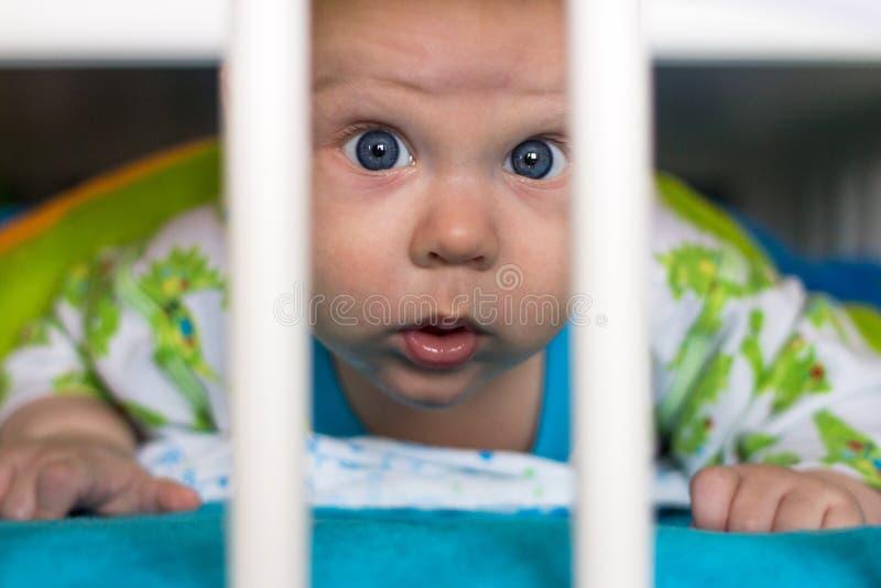 Baby with big blue eyes in a crib. Baby boy with big blue eyes in a crib stock photography