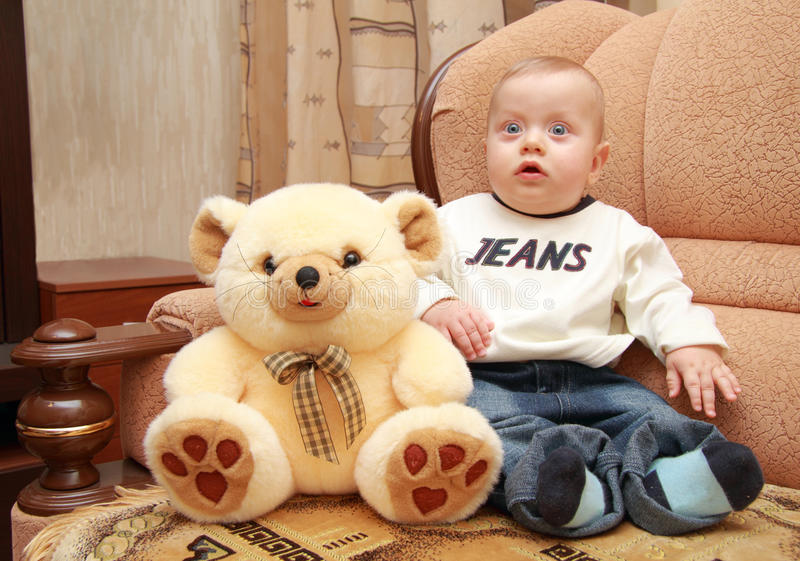 Baby with big blue eyes sit next to teddy bear royalty free stock photo