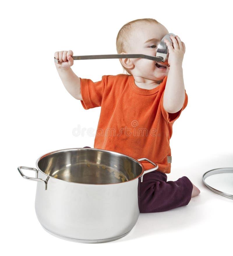 Baby with big cooking pot stock photos