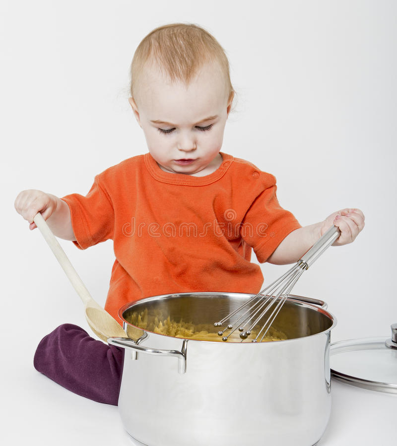 Baby with big cooking pot royalty free stock photography