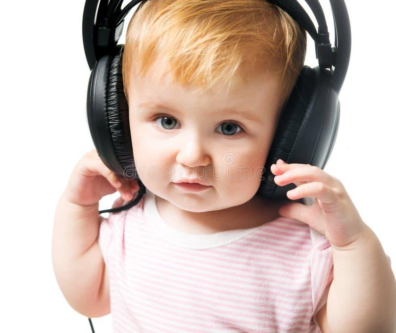 Baby in big headphones stock photo