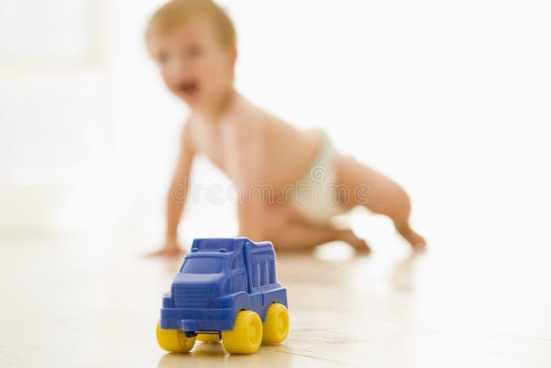 Baby binnen met stuk speelgoed vrachtwagen stock foto