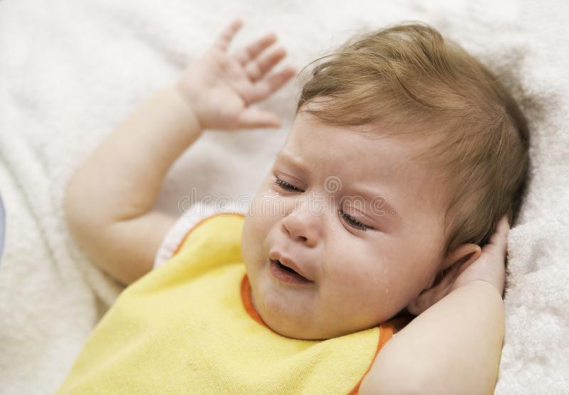 The baby in a bip is crying and refuses to eat. Child`s hysterics. Closeup portrait of crying baby. The baby in a yellow bip is crying and refuses to eat. Child` stock photos