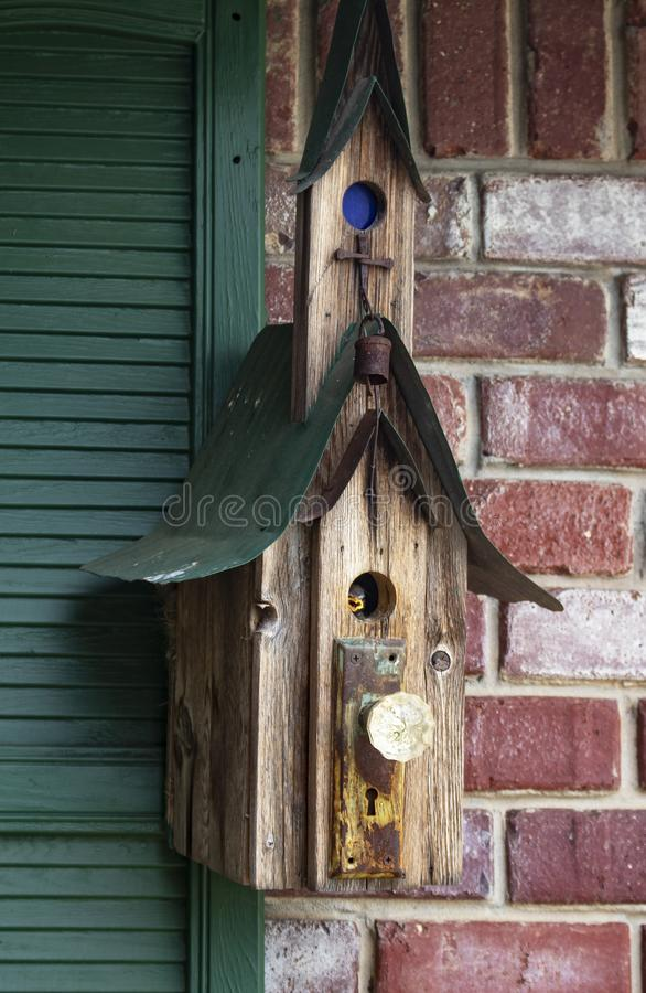 Baby bird waiting for mother inside round door of rustic bird house hung on brick wall and green shutters stock image