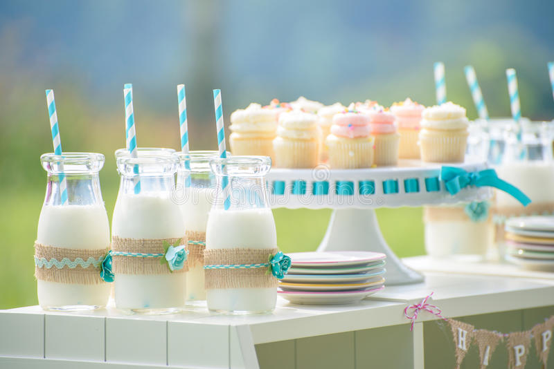 Baby birthday decoration with bottles of milk and cupcakes royalty free stock photography