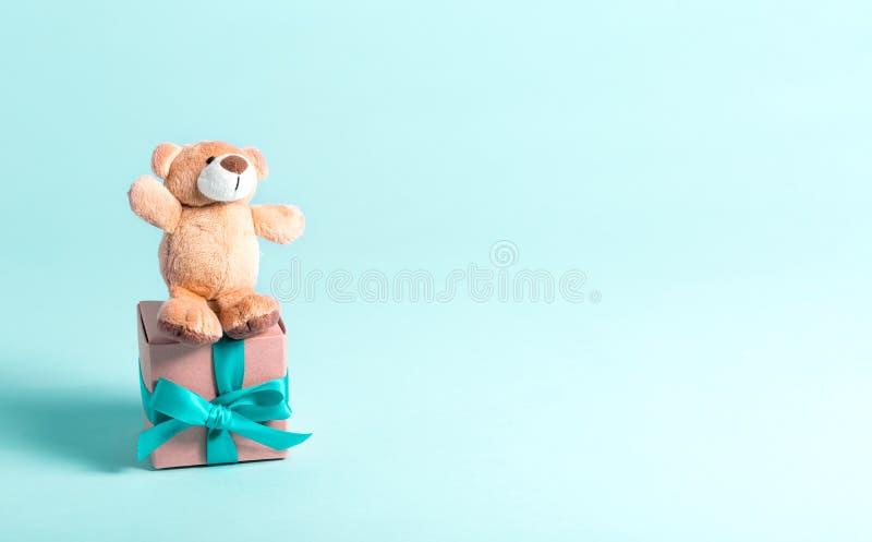 Baby birthday theme with teddy bear and present. Baby birthday theme with teddy bear and gift box on a blue background stock photos
