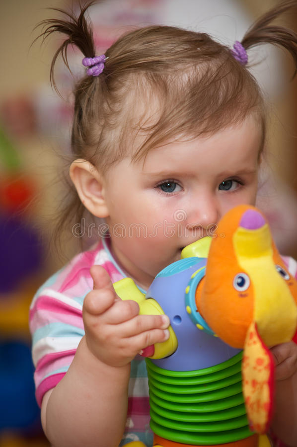 Baby biting on toy. Cute baby girl biting on her toy royalty free stock image