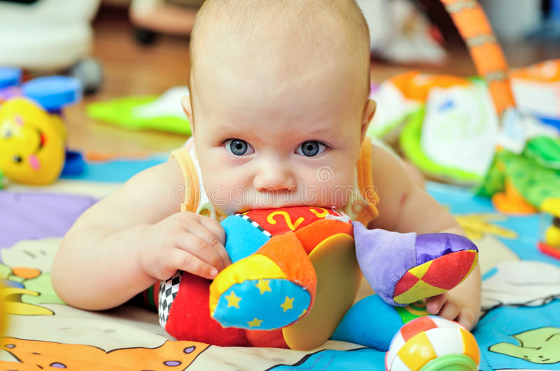 Baby biting toy. Portrait of sweet blue-eyed baby stock images