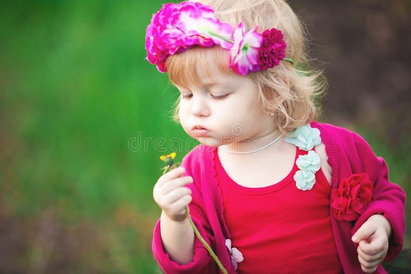 Baby in blühendem Frühling arbeitet Löwenzahn im Garten lizenzfreie stockfotografie